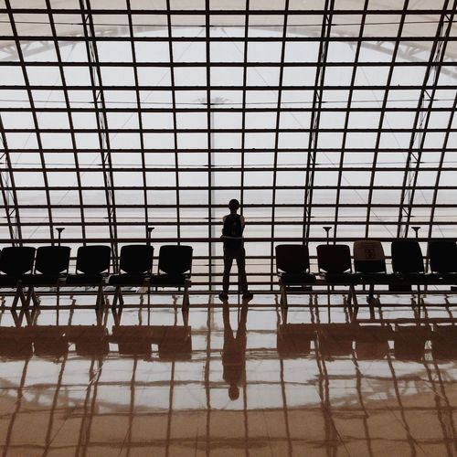 Rear View Of Man Standing At Departure Area Against Window With Reflection On Tiled Floor At Airport
