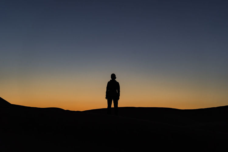 Silhouette Sky One Person Sunset Standing Lifestyles Beauty In Nature Rear View Tranquil Scene Tranquility Outdoors Looking At View Dusk Desert Desert Landscape Sahara Travel Destinations North Africa Middle East Real People Full Length Afterglow Dusk Colours Dusk Sky Dusk Light