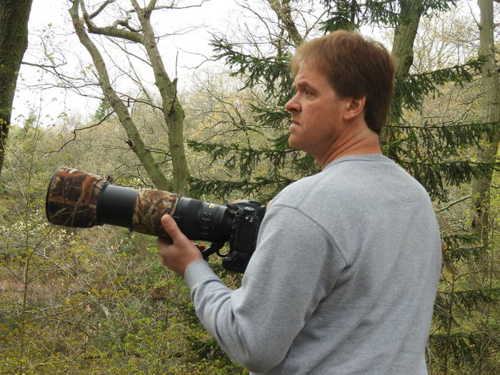 Side view of man photographing with digital camera in forest