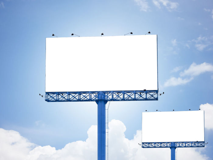 Low angle view of blank billboards against blue sky