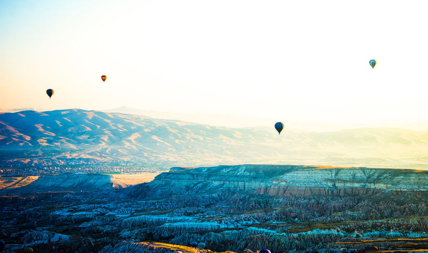 Cappadocia Hot Air Balloons Adventure Air Vehicle Ballooning Festival Beauty In Nature Day Flying Hot Air Balloon Landscape Mid-air Mountain Multi Colored Nature No People Outdoors Parachute Rock Hoodoo Scenics Sky Sunrise Tranquil Scene