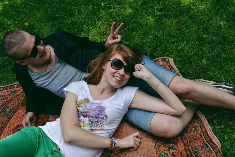Portrait of happy young couple relaxing on field at park