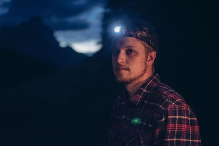 Portrait of young man with illuminated headlamp standing in forest at night
