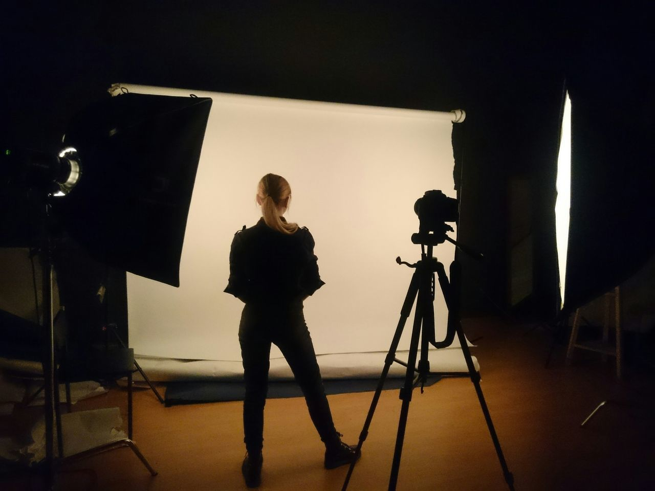Full length rear view of woman standing by tripod in studio