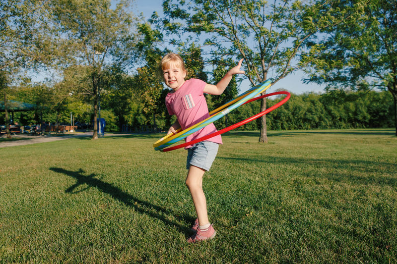 Full length of smiling girl playing with plastic hoop on grassy land