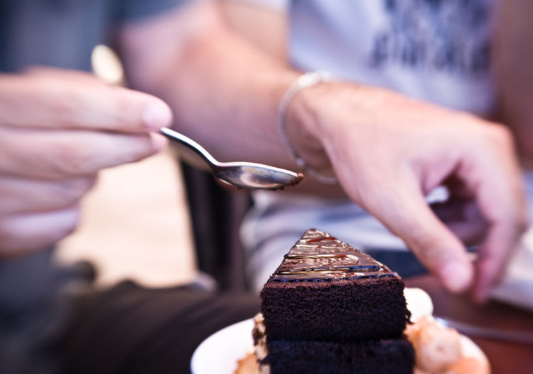 Midsection Of Person Holding Spoon Over Cake