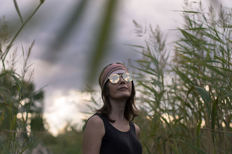 Mature woman wearing sunglasses standing amidst plants against cloudy sky during sunset