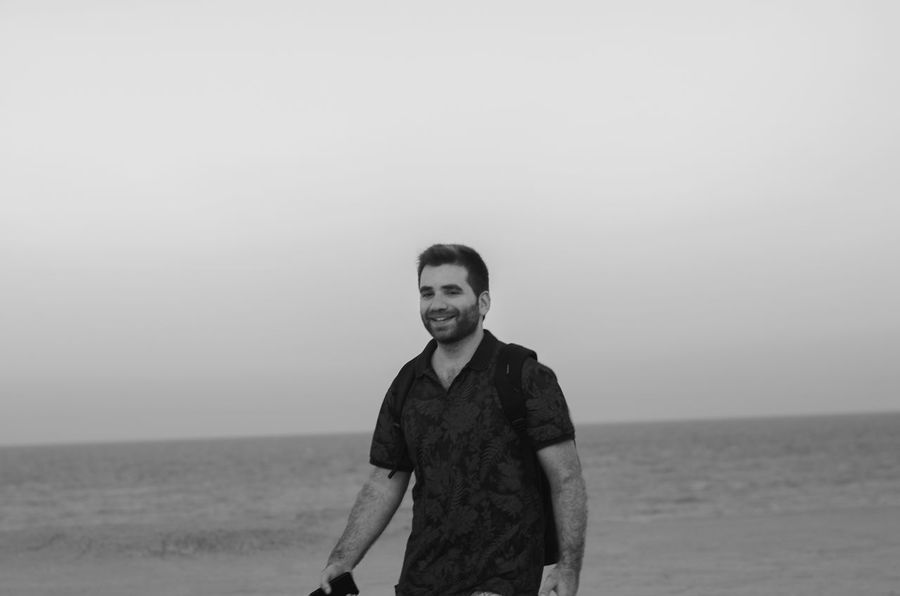Water Sea One Person Standing Looking At Camera Portrait Young Adult Real People Leisure Activity Lifestyles Casual Clothing Young Men Smiling Front View Sky Beauty In Nature Waist Up Scenics - Nature Land Horizon Over Water Outdoors