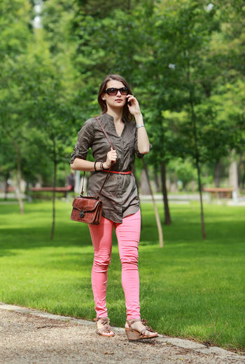 Young woman on the phone walks alone in a city park. One Person Full Length Front View Leisure Activity Lifestyles Holding Casual Clothing Green Color Outdoors Phone Phone Call Call Woman Woman Using A Phone Walking Walk Stroll Strolling Summer Summertime Spring Springtime