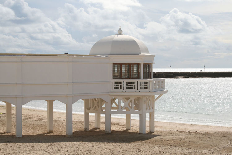 Built Structure On Beach Against Cloudy Sky