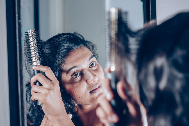 lady combing her hair looking at her image at mirror. Adult Brown Hair Emotion Hair Hairstyle Headshot Human Face Indoors  Lady, Women, Girl, Female, Model, Mirror, Image, Reflection, Hair, Style, Hair Styiling, Combing, Brush, Comb, Hair Brush, Make Up, Looks, Beauty, Admire, Pimple, Indian, Dark Hair, Morning, Attractive, Smile, Woman, Clear, Relaxing, Calm, Lifestyle, Apar Lifestyles Looking Mid Adult Mirror People Portrait Real People Reflection Window Women Young Adult Young Women
