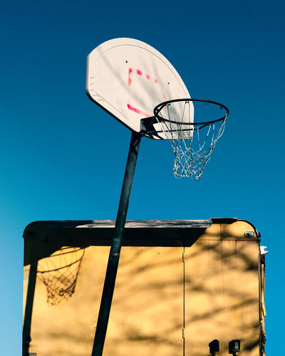 A basketball hoop in a neighborhood. Basketball Hoop Basketball Hoop Basketball - Sport Sport Sky Low Angle View Net - Sports Equipment Outdoors Sports Equipment Court Basketball - Ball Blue Yellow