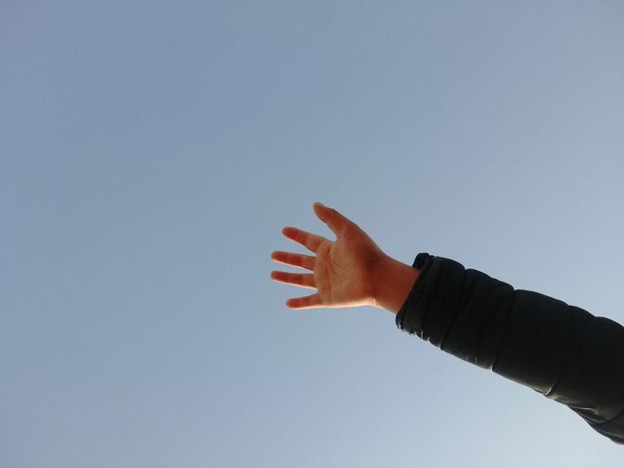 Cropped hand of person against clear sky