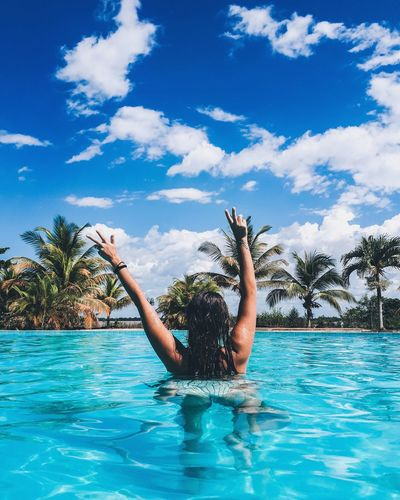 Rear view of woman with arms raised in swimming pool against blue sky during sunny day