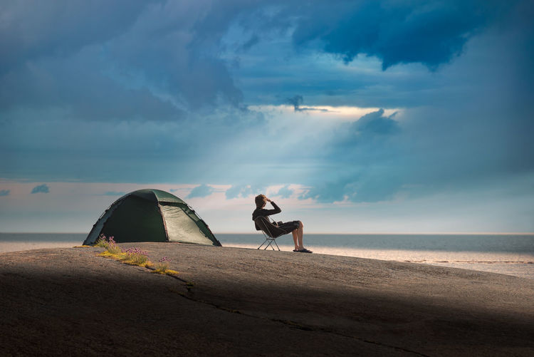 Man camping at beach against cloudy sky during sunset