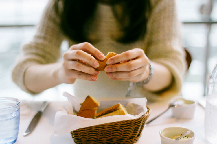 Midsection of woman holding fortune cookie over basket