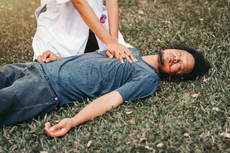 Midsection of couple lying on field