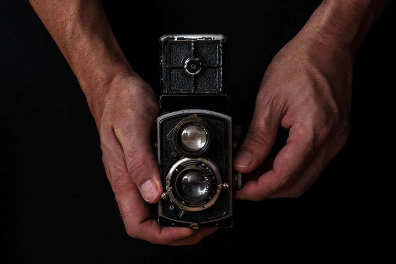 Close-up of hand holding camera against black background