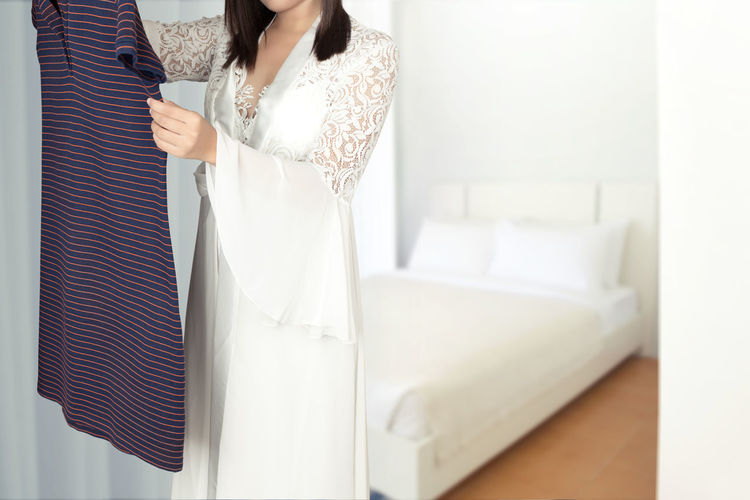 Asian woman in long white silk nightgown stand choosing clothes in wardrobe at home Choose T-shirt Clothes Selection Clothing Change Shirt Wear Apparel Garment Nightgown Silk White Lifestyles One Person Indoors  Women Adult Real People Standing Domestic Room Young Adult Midsection Young Women White Color Home Interior Window Dress Casual Clothing Hair Hairstyle Beautiful Woman