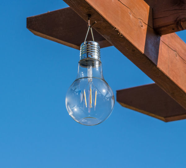 Low angle view of light bulb against clear blue sky