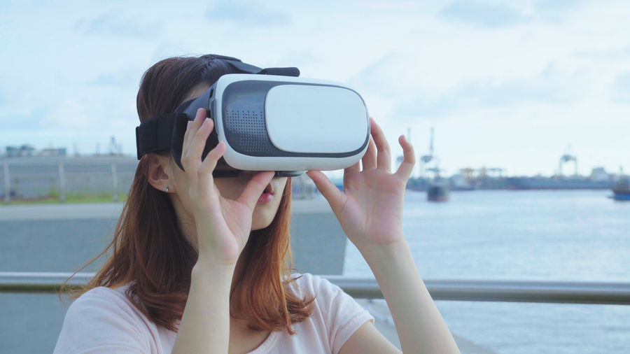 Beautiful woman using virtual reality simulator while standing on bridge over river in city