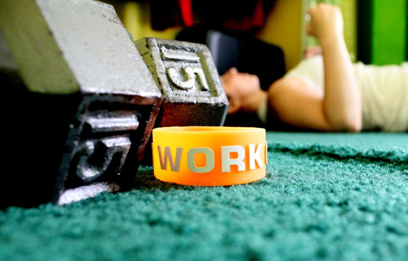 Text On Wristband With Dumbbells By Woman Exercising At Home