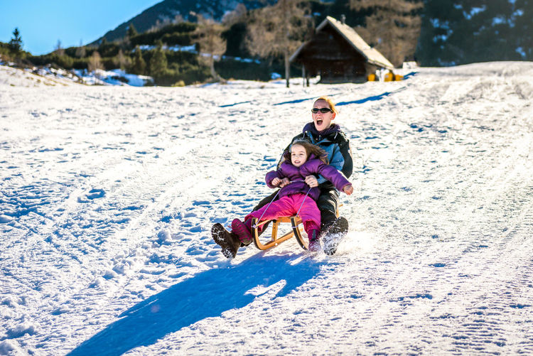 Portrait of mother and daughter sliding on snow