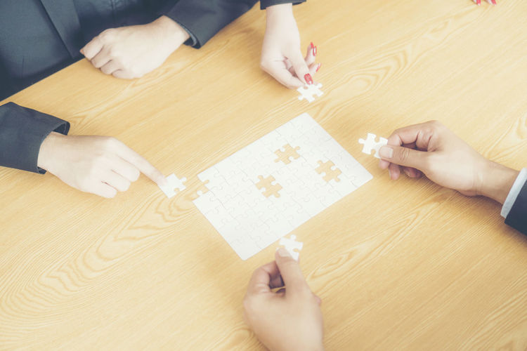 High Angle View Of Business People Arranging Jigsaw Puzzle On Table