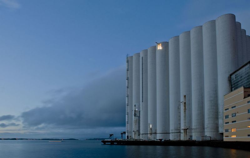 Panoramic view of silo and  sea against sky at dusk