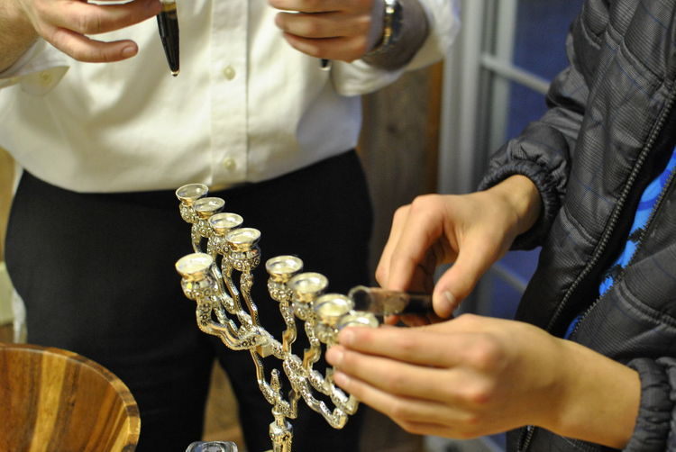Midsection of person putting candle in menorah