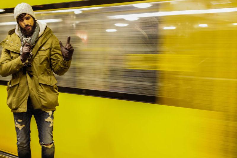 Man gesturing against blur metro at subway station