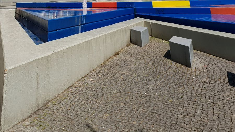 Relaxation cornerat the fountain in Mülheim an der Ruhr Cube Grey Triangle Shape Seat Relaxation Area Corner Colourful Fountain Copy Space City Marketing In Front Centered Zoom Close-up Diagonal Mülheim An Der Ruhr Mülheim (Ruhr) Mülheim Northrhine Westphalia Close Up Diagonal Line Water Red Blue Yellow Industry Factory Architecture Concrete Concrete Wall
