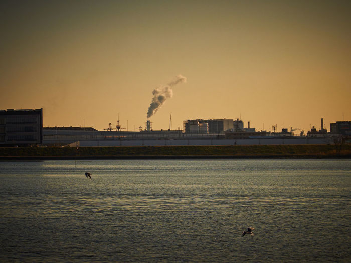 Factory Emitting Smoke By Sea Against Sky During Sunset