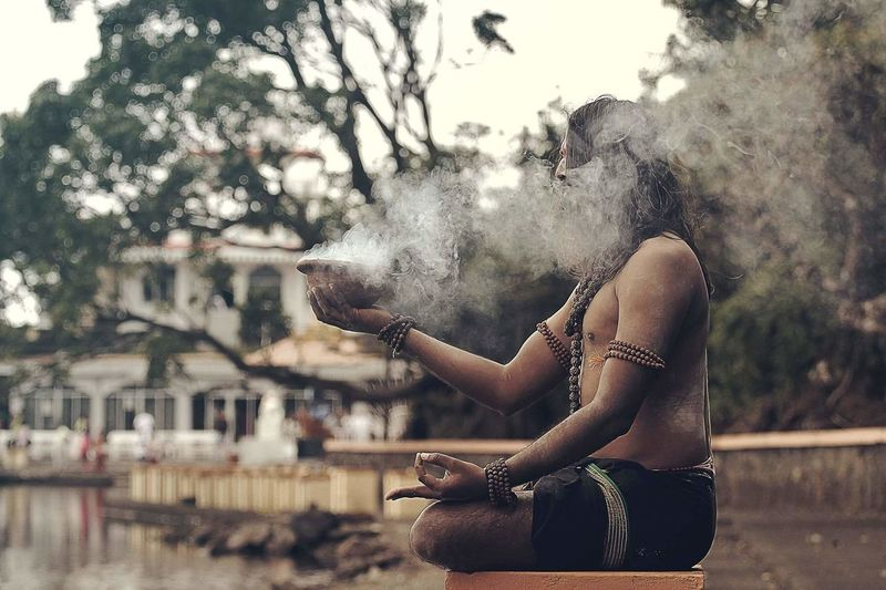 Side view of sadhu sitting with smoke emitting container on stool