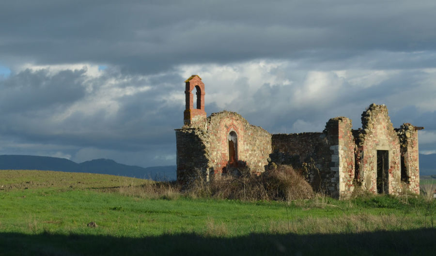 Old ruin building on field against sky