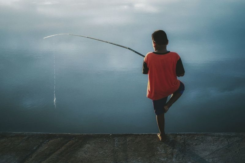 Rear view of boy standing in sea