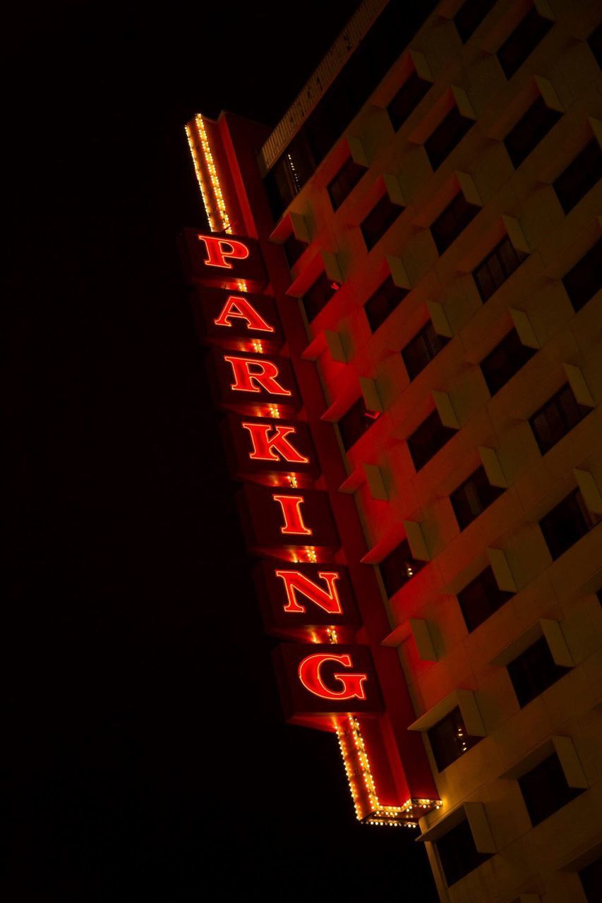 Low Angle View Of Illuminated Neon Parking Sign On Building At Night