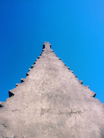 Low angle view of cross on spire against blue sky