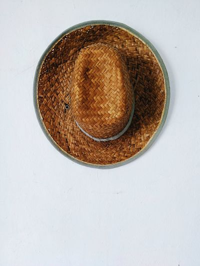 Directly above shot of hat on table against white background