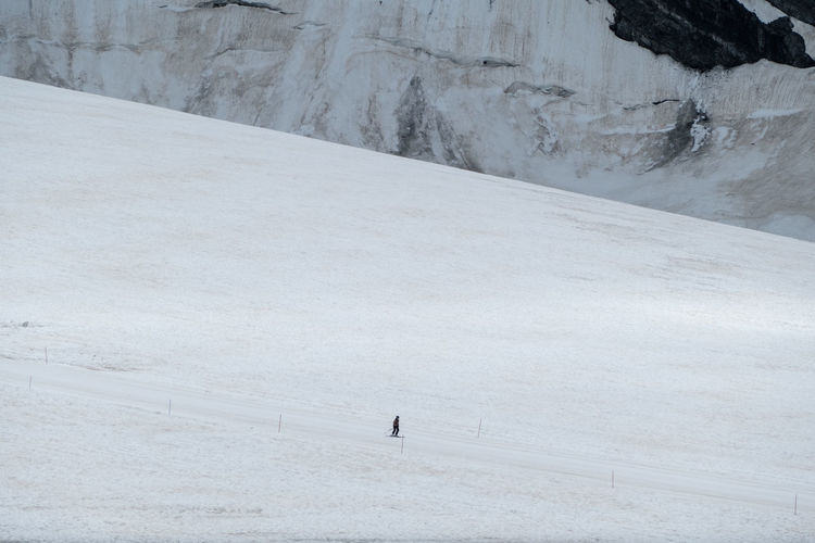 High angle view of person walking on snow covered land