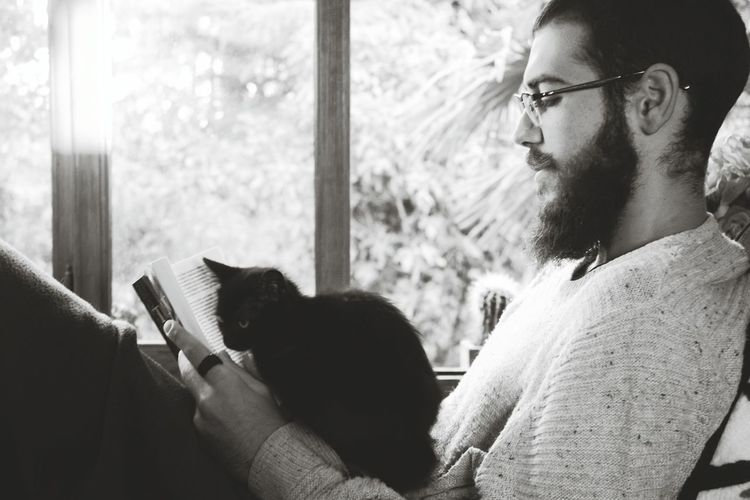 Only Men Adults Only Indoors  Mid Adult Men Day Eyeglasses  Beard Relaxation People Adult One Person One Man Only Men Long Sleeved Young Adult Cats Reading & Relaxing