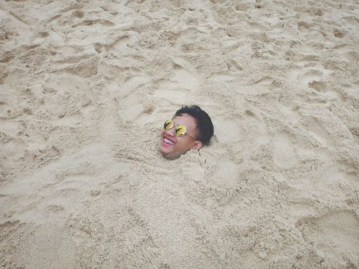 High angle view of smiling man buried in sand