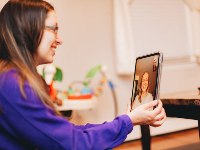 Side view of woman talking on video call at home