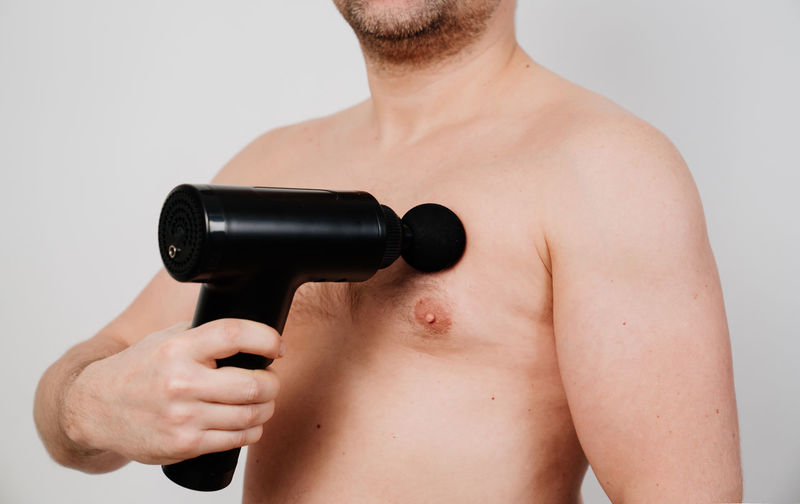 Midsection of shirtless man using percussion massager