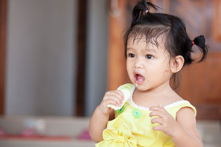 Close-up of cute baby girl eating fruit