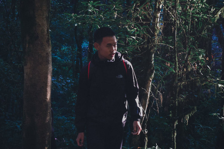 Full length of young man looking at forest