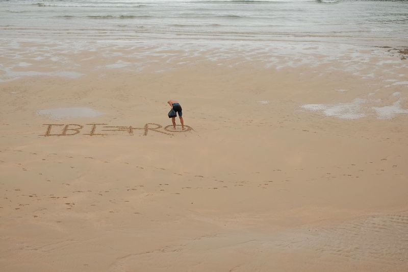 Rear view of man writing on sand at beach