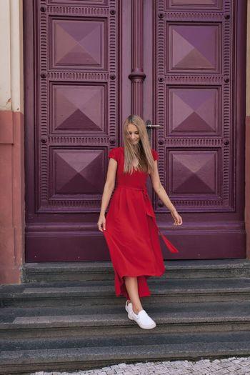 Full length of woman standing against red door
