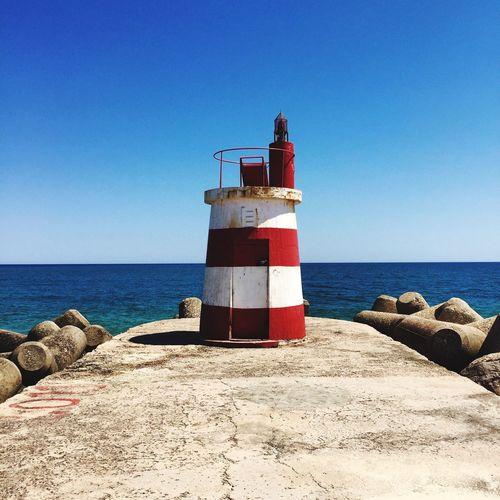 Lighthouse on pier against clear blue sky