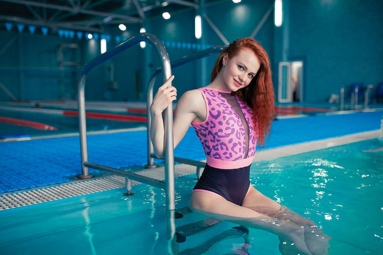 Beautiful sportive girl in the swimming pool. Fit redhead caucasian woman health care leisure. Woman Girl Redhead Redhair Sport Swimming Swimming Pool Indoors  Fitness Fit Fitness Training Fitnessmodel Motivation Sportive Sportivegirl Caucasian Females Trainer Coach Tourquise Water Swimsuit Young Adult Young Women Healthy Lifestyle Lifestyles Leisure Activity Aqua Aerobics Rehabilitation Pool One Person Women Adult Smiling Swimwear Real People Looking At Camera Front View Portrait Teenager Hairstyle Beautiful Woman